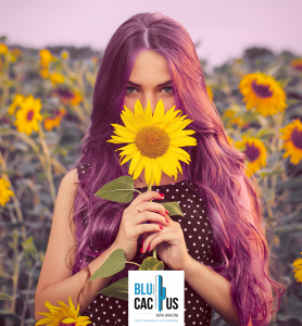 BluCactus - Girl with long hair smelling a sunflower with light background