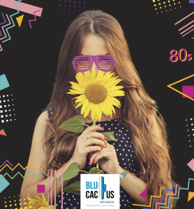 BluCactus - Girl with long haie smelling a sunflower with purple glasses